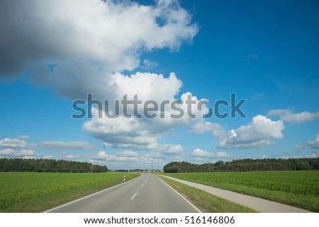 country road with bikeway  in rural landscape and blue sky with cumulus clouds