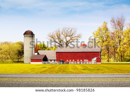 Country Road with Red Farm in Background - stock photo