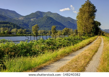 country road with steps by a river - stock photo