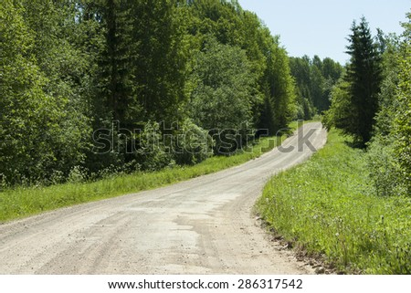 Country sandy road and green trees in countryside