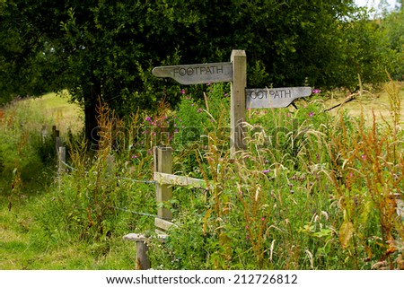 Country Stile. Overgrown footpath stile. Wild flowers and long grasses partially hide a typical stile.   - stock photo