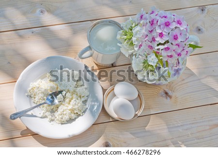 Country still life in white tones and flat lay with dairy products and eggs.