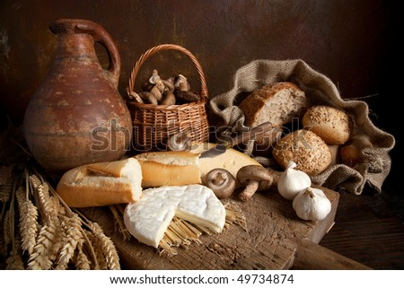 Country still life with bread, cheese, mushrooms and wine in an antique jar