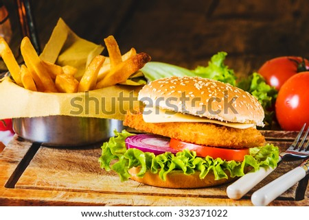 Country-style dish on a wooden table with a chicken burger and fried chips