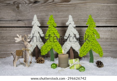 Country style wooden christmas decoration in apple green and white with candle and moose. - stock photo