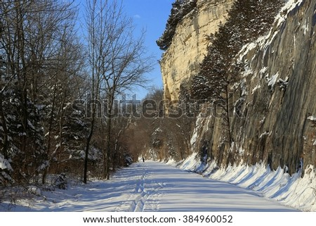 Country trail after a snow storm; high bluffs on the right - stock photo