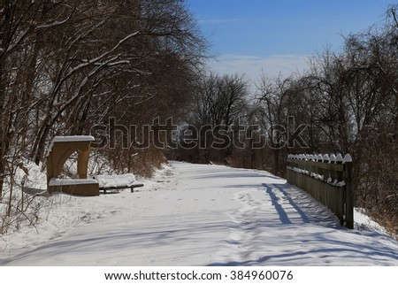 Country trail after a snow storm; wooden gate on the right, a bench of the left  - stock photo