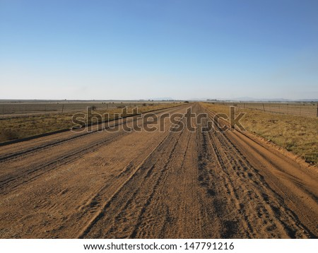 Country view of a long and straight dirt road leading into the distant horizon - stock photo
