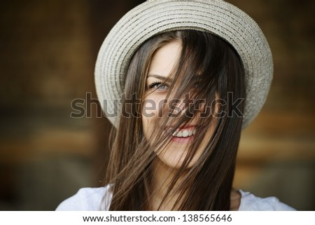Country young woman with cowboy hat with windy hair on her face - stock photo