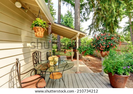 Countryside house exterior with small patio area. Porch decorated with flower pots