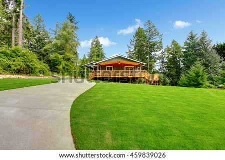 Countryside house with wooden walkout deck and patio area - stock photo