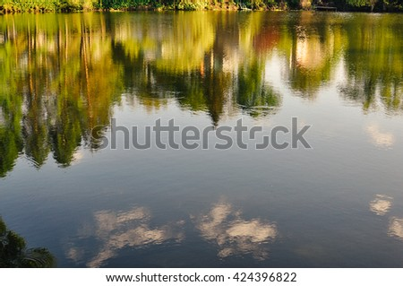 Countryside landscape: sky, trees and roofs of rural houses reflected in the pond water: concept of calm quiet life