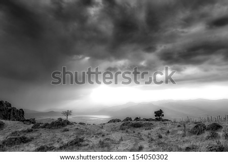 Countryside road between dry straw in a spectacular summer sunset - Black and white 2 - stock photo