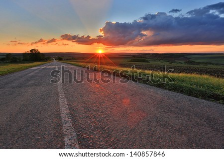 countryside road on sunset sky background - stock photo