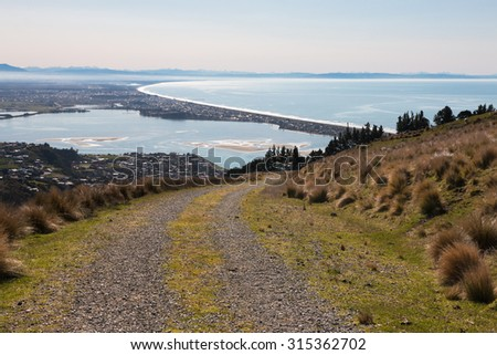 Countryside road up hill with view to the ocean, Christchurch, New Zealand - stock photo