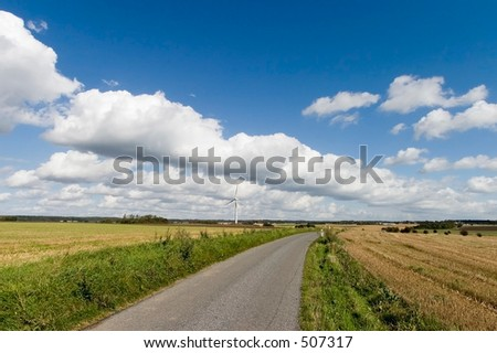 Countryside road. Windmill on on a field on a sunny day with nice clouds, Denmark - stock photo