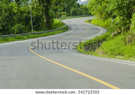 Countryside road with trees on both sides. - stock photo