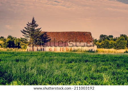 Countryside scenery with an old and weathered barn - stock photo