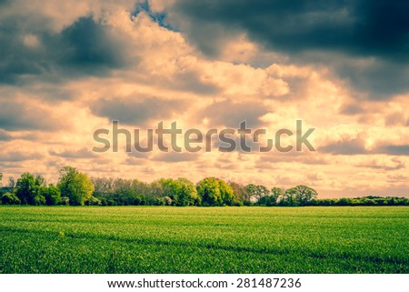 Countryside scenery with dark clouds over a field - stock photo