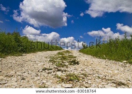 Countryside stone road in fields and blue sky with clouds - stock photo