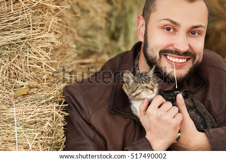 Countryside weekend concept. Young smiling relaxed man in brown leather jacket sitting near straw bales and holding little cat. Copy-space. Close up. Outdoor shot