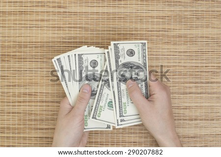 counts money dollars hands over a table from above - stock photo