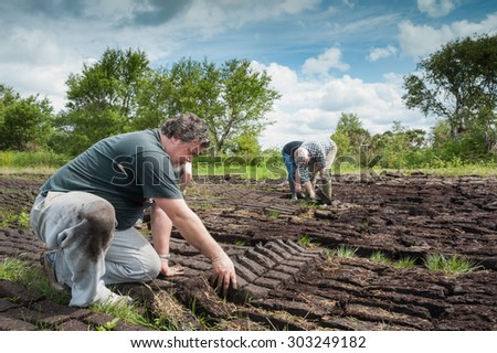 County Kerry, Ireland - May 31, 2014: Workers cultivating a peak bog field outside the town of Listowel in County Kerry