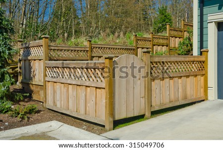 County style wooden fence and house entrance. - stock photo
