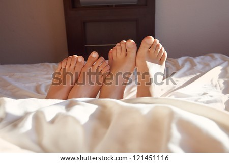 Couple acting naughty in bed - View of a couple's feet in bed