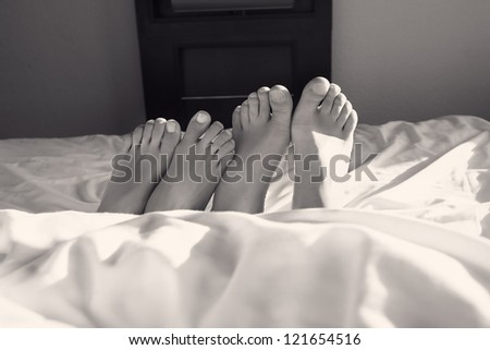 Couple acting naughty in bed - View of a couple's feet in bed - stock photo