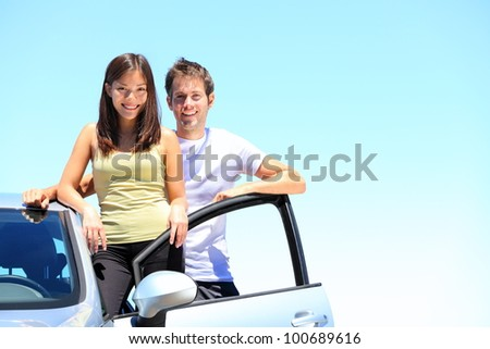 Couple and new car smiling happy standing outside on sunny summer day during road trip travel vacation. Young interracial couple in their twenties, Asian woman, Caucasian man.