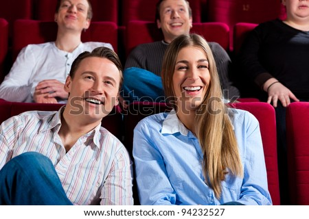Couple and other people, probably friends, in cinema watching a movie; it seems to be a funny movie - stock photo
