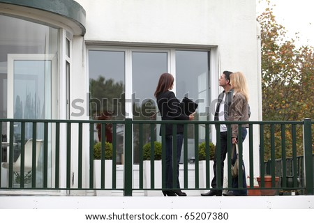 Couple and real-estate agent in front of house for sale - stock photo