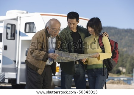 Couple and senior father reading map outside RV - stock photo