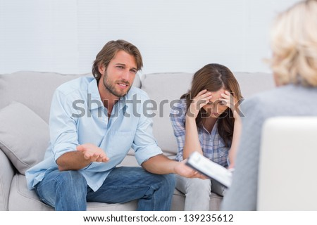 Couple arguing and crying on the couch during therapy session - stock photo
