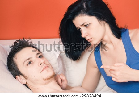 Couple arguing in bed, woman is right - stock photo