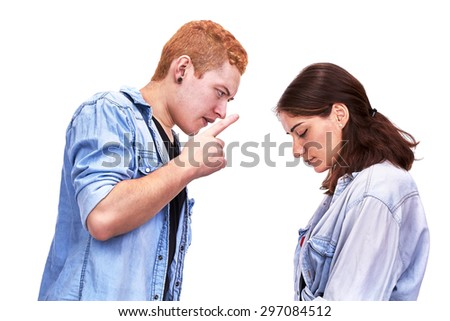 Couple arguing: the husband is pointing and accusing and the wife is accepting the blame submissively looking down, isolated on white