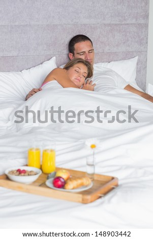 Couple asleep with breakfast tray on bed at home in bedroom - stock photo