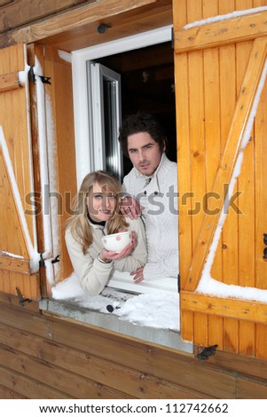 Couple at a window of a cottage - stock photo