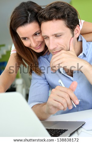 Couple at home looking at bank account on internet - stock photo