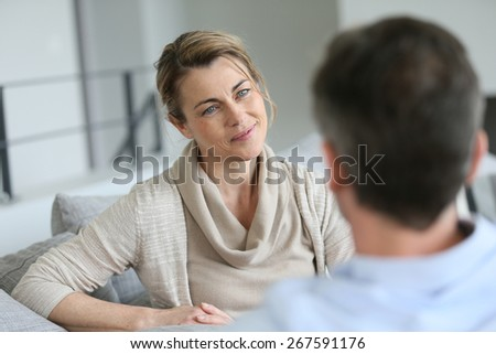 Couple at home sitting in sofa and having a talk - stock photo