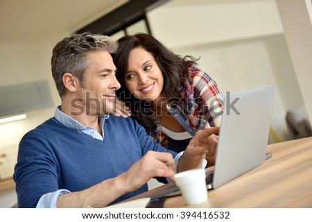 Couple at home using laptop computer