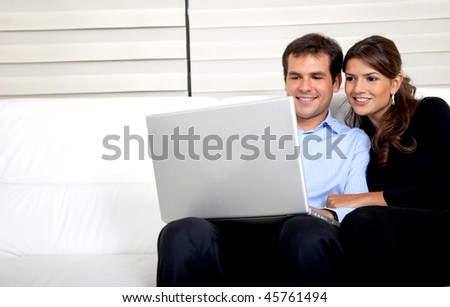 Couple at home working on a laptop - stock photo