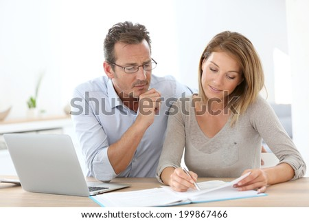 Couple at home working on laptop computer - stock photo
