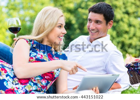 Couple at picnic in park with red wine and tablet computer