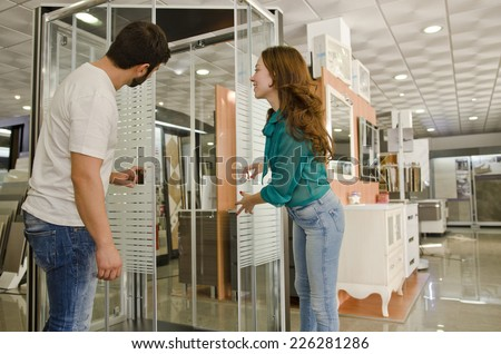 Couple at plumbing store looking shower enclosures and furniture. - stock photo