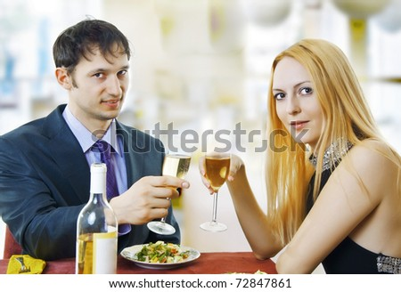 Couple at restaurant on dinner party. They're looking at the shot and raise a toast. - stock photo