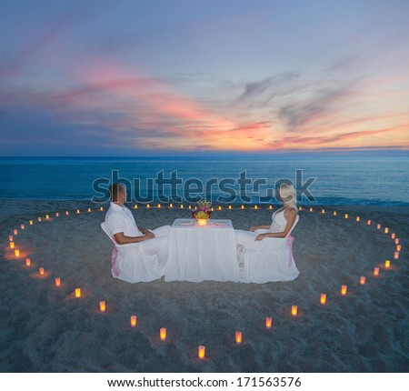 couple at romantic dinner with candles heart on sandy sea beach - stock photo