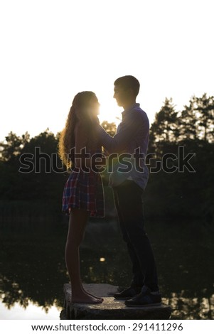 couple at sunset near the river - stock photo