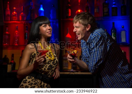 Couple at the bar having drinks - stock photo